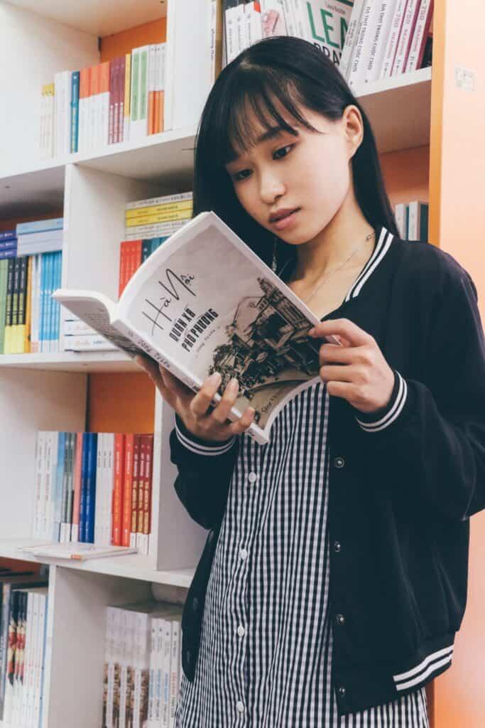 dziewczynka czyta książkę w pokoju ucznia